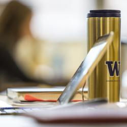 Items, including a gold colored UW branded insulated mug, on a desk.